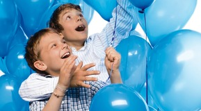Two children with helium filled balloons